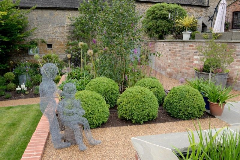 Buxus topiary in a terraced Cotswold garden with sculpture and alliums