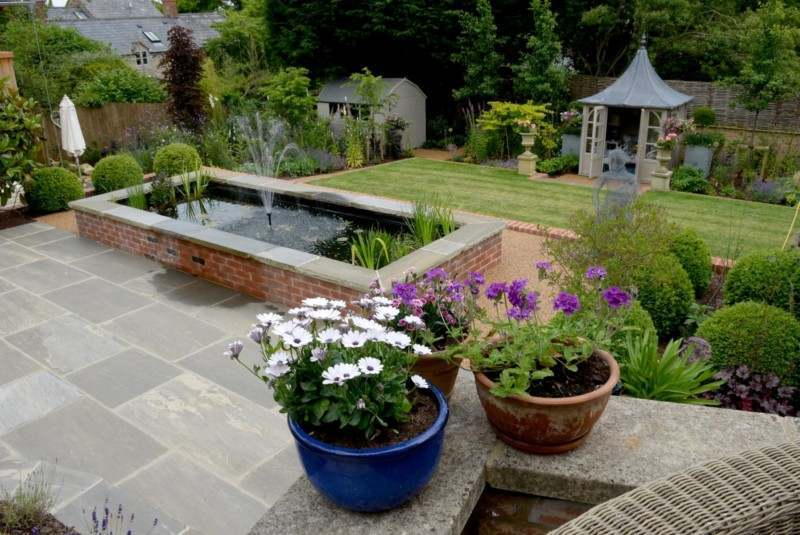 Raised formal water feature with central fountain in a terraced Cotswold garden